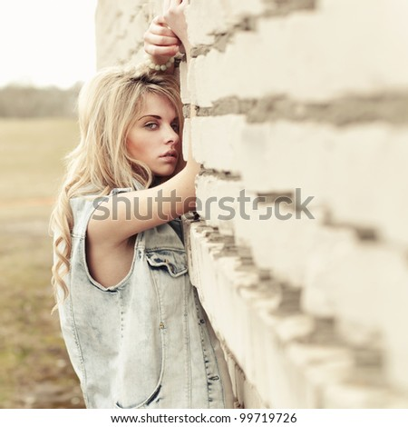 beautiful young woman near the wall