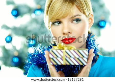Beautiful young woman next to christmas tree on white background