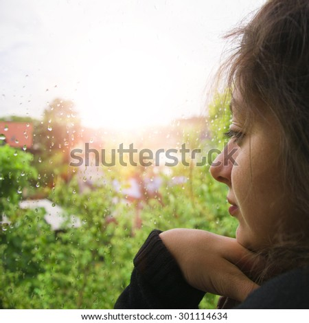beautiful young woman of Asian appearance looks out the window as the rain falls. The window in rain drops with green trees as background. Sadness and search. The girl has big black eyes. - stock photo