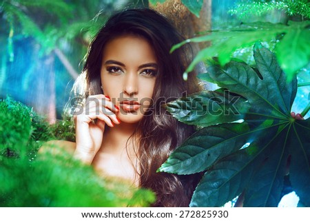 Beautiful young woman on a background of green plants. Spa. Healthcare, body care. - stock photo