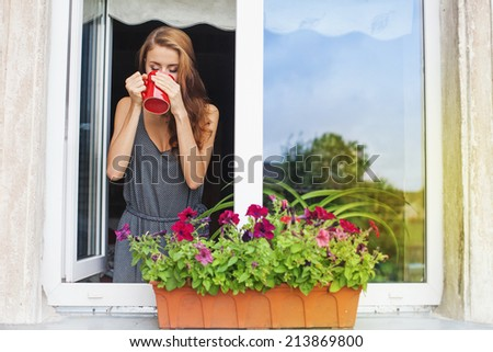 Beautiful young woman on a balcony with cup of coffee - stock photo