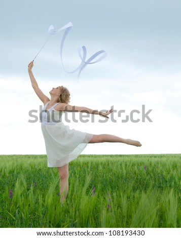 Beautiful young woman  on a green meadow with a gymnastic ribbon