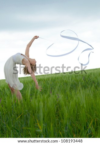 Beautiful young woman  on a green meadow with a gymnastic ribbon - stock photo