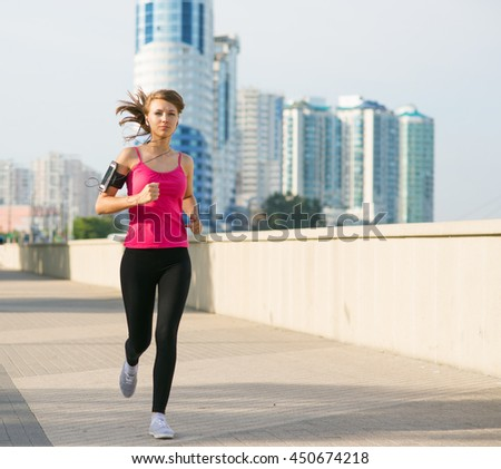 beautiful young woman on a morning jog in the city listening to music in headphones from smartphone fixed in her pocket on the arm - stock photo