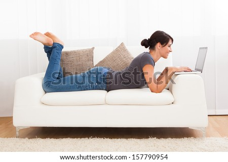 Beautiful Young Woman On A Sofa Working With A Laptop - stock photo