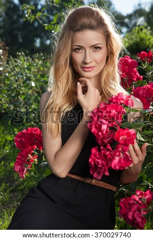 Beautiful young woman on a walk, the girl in flowers. Woman and flowers.Beautiful young woman and flowers.Stylish fashionable woman in the highlights