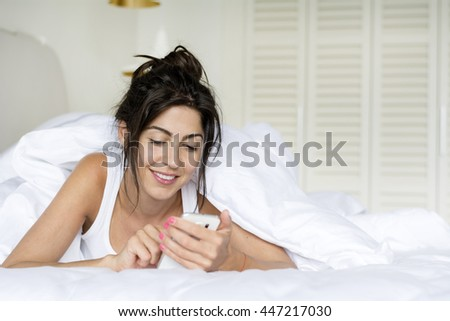 beautiful young woman on a white linen in bed at home sending message - stock photo