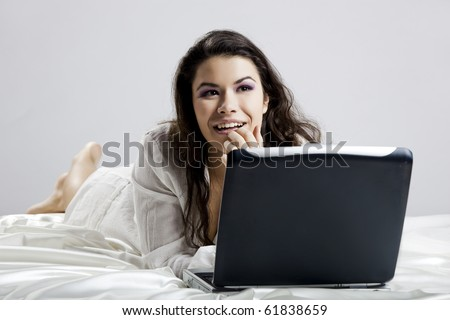 Beautiful young woman on bed working with a laptop - stock photo
