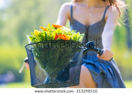 Beautiful young woman on bike with flower in park