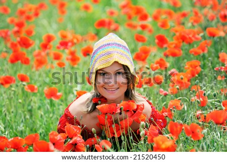 beautiful young woman on field with poppies - stock photo