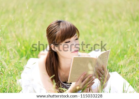 Beautiful young woman on green field. Portrait of asian. - stock photo