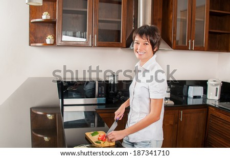 Beautiful young woman on kitchen cuts salad