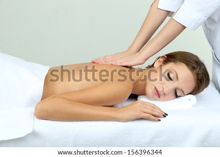 Beautiful young woman on massage table in cosmetic salon close up - stock photo