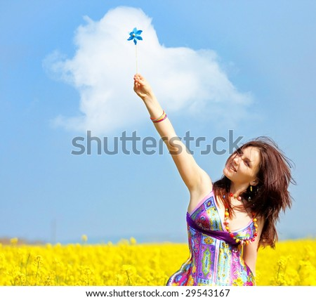 beautiful young woman on rapeseed (canola) field - stock photo