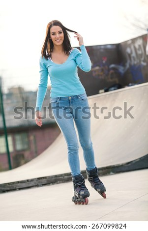 Beautiful young woman on rollerblades in a skateboard park - stock photo