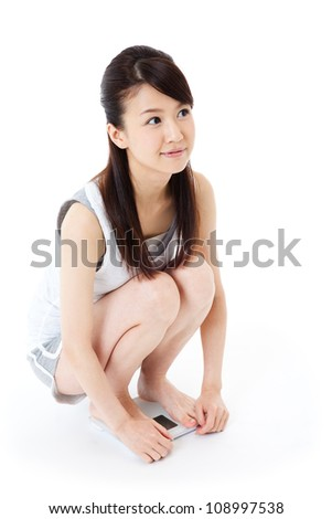 Beautiful young woman on scale. Portrait of asian. - stock photo