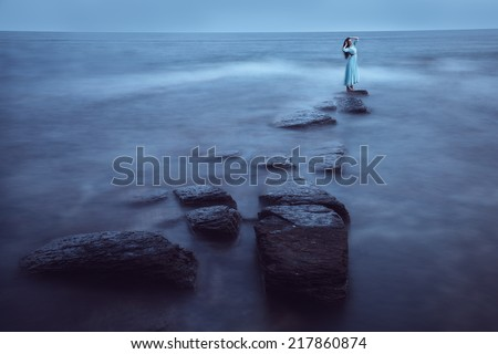 Beautiful young woman on sea in twilight. Long time exposure - stock photo