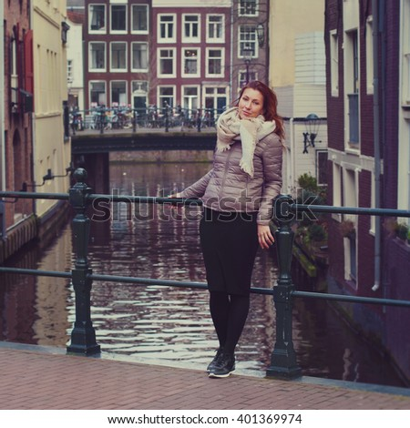 Beautiful young woman on the bridge in Amsterdam looks at camera. Copy space.