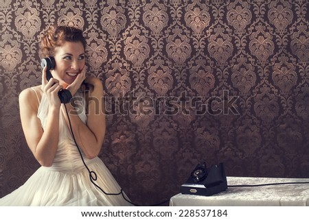 Beautiful young woman on the phone in living room in her English house - stock photo