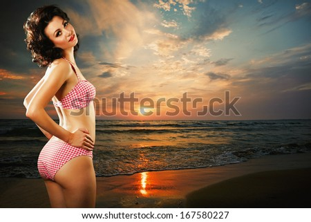 Beautiful young woman on the sea beach at sunset