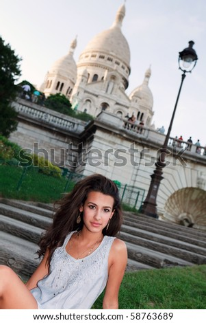 Beautiful young woman on the steps of Sacre-Coeur Basilica in the Montmartre area in Paris, France. - stock photo