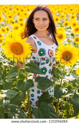 Beautiful young woman on the sunflowers field.