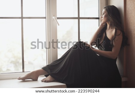 Beautiful young woman on the window - stock photo