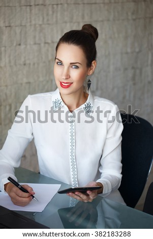 Beautiful young woman on the workplace using a digital tablet - stock photo