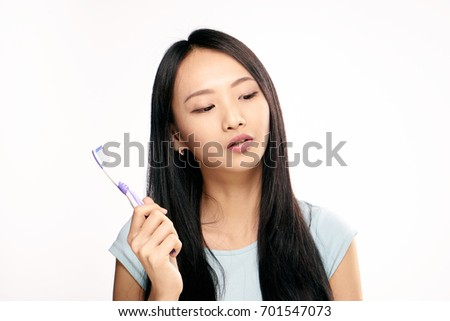 Beautiful young woman on white isolated background holds a toothbrush, Asian.