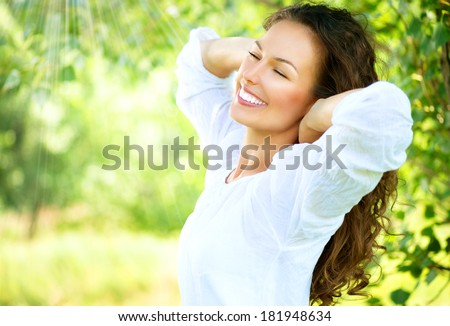 Beautiful Young Woman Outdoor. Enjoy Nature. Healthy Smiling Girl in the Spring Park. Sunny day  - stock photo