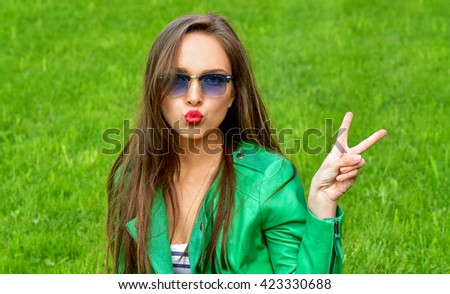 Beautiful Young Woman Outdoors. Blowing lips kiss.  Fashion woman in sunglasses outdoor. - stock photo