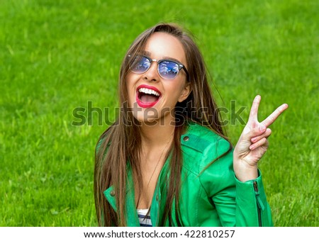 Beautiful Young Woman Outdoors. Enjoy Nature. Healthy Smiling Girl in Green Grass. Fashion woman in sunglasses outdoor.