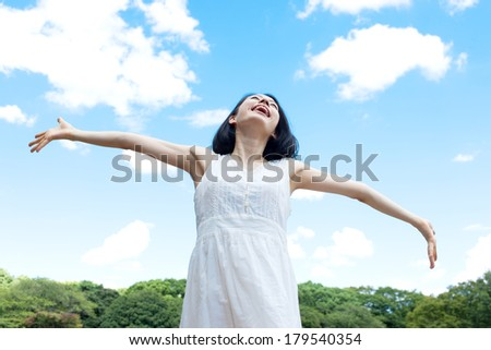 Beautiful young woman over blue sky and forest