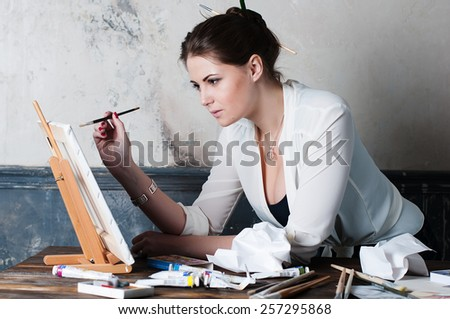 beautiful young woman painter in her studio, selective focus - stock photo