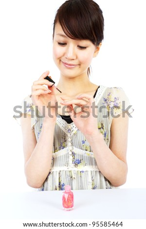 Beautiful young woman painting nails. Portrait of asian woman.