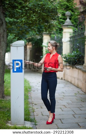 Beautiful young woman paying for parking - stock photo