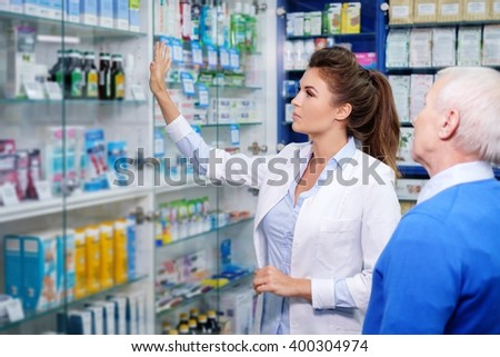 Beautiful young woman pharmacist showing drugs to senior man customer in pharmacy. - stock photo