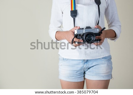 Beautiful young woman photographer holding retro camera