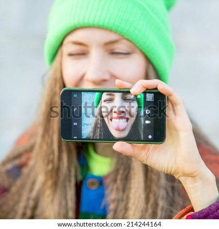 Beautiful young woman photographing herself with phone. Cute smiling young caucasian teenage girl taking a selfie outdoors. daylight - stock photo