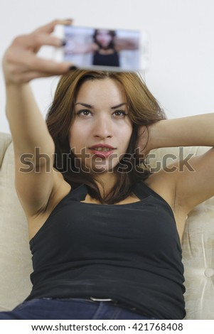 Beautiful young woman photographing herself with phone sitting in sofa - stock photo