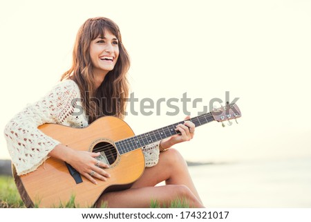 Beautiful young woman playing guitar on beach at sunset, fashion lifestyle