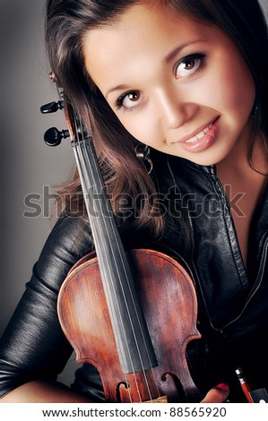 Beautiful young woman playing her violin with expression. Over grey ba?kground.