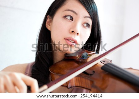 beautiful young woman playing violin - stock photo