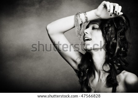 beautiful young woman playing with bracelet, bw, studio shot - stock photo