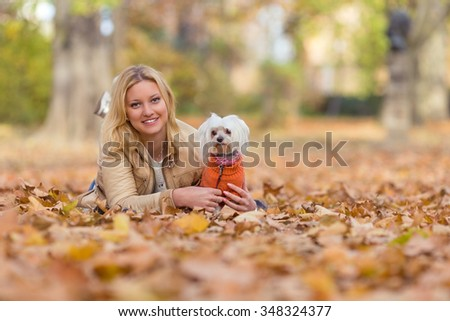 Beautiful young woman playing with her dog in autumn leaves