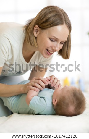 Beautiful young woman plays with newborn baby