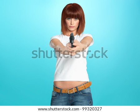 beautiful, young woman pointing a gun at the camera, on blue background