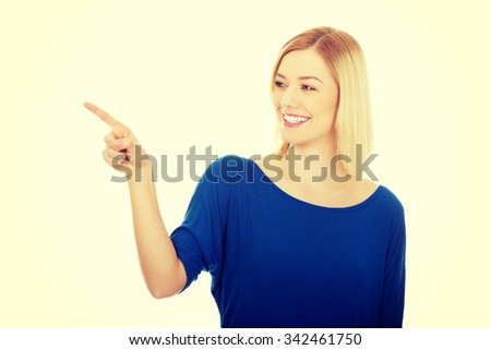 Beautiful young woman pointing aside. - stock photo