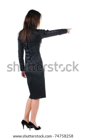 Beautiful young woman pointing at wall. Rear view. - stock photo