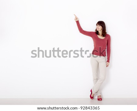 Beautiful young woman pointing to the right side with copyspace, against a white wall - stock photo